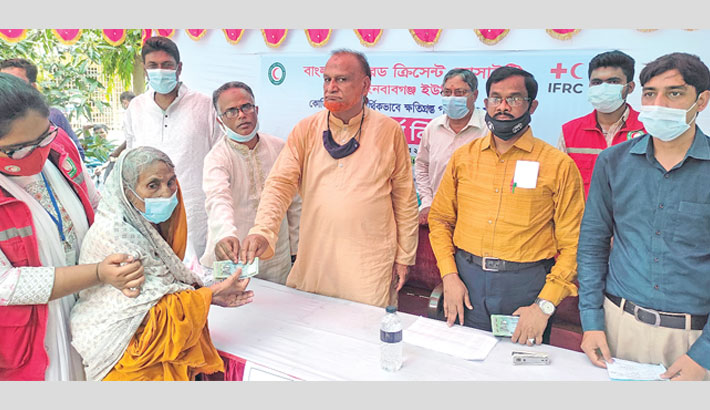 Vice Chairman of Chapainawabganj district unit of Bangladesh Red Crescent Society Md Abdul Hakim and Chapainawabganj Zila Parishad Chairman (Acting) Md Ashraful Haque distributes cash aid among corona-hit poor people on the premises of zila parishad complex in the district town on Sunday. – Sun Photo