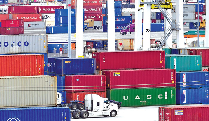 Container trucks make their way past stacked containers at the Port of Los Angeles in San Pedro, California. The US trade deficit fell in July for the first time in three months, the Commerce Department said September 2, 2021, as the vaccine-fueled surge in American consumer demand ebbed and exports picked up.