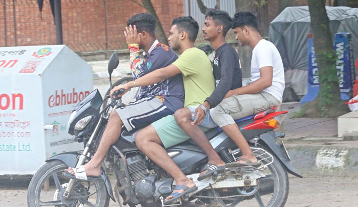 A youth rides a motorbike with three riders without helmets and facemasks, risking their lives and violating traffic rules. The photo was taken from Dhaka University campus on Tuesday.—Md Nasir Uddin