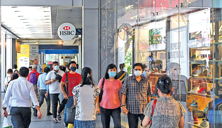 People walk past a shopping mall along Orchard Road in Singapore on Tuesday.