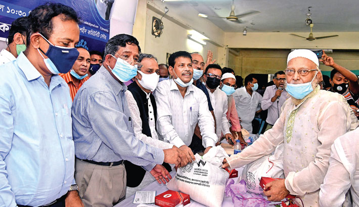 Agriculture Minister Dr Md Abdur Razzaque distributes food items among the distressed on Nawabganj Sath Shaheed Community Centre premises at Lalbagh in the capital on Wednesday. Engineers Institution, Bangladesh (IEB) and North-West Power Generation Company jointly organised the programme.