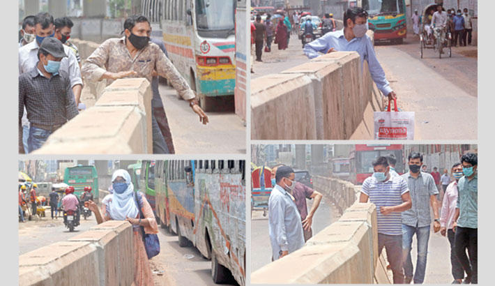 People are crossing a road divider at Topkhana Road in the capital on Wednesday risking their lives as vehicles are running on both sides.  MD NASIR UDDIN