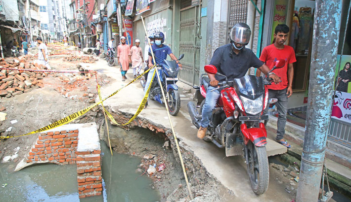 After installation of the sewerage pipes, Abul Hasnat Road in Old Dhaka has been left in this bad condition for long, causing sufferings for locals and pedestrians. The photo was taken on Thursday. — Reaz Ahmed Sumon