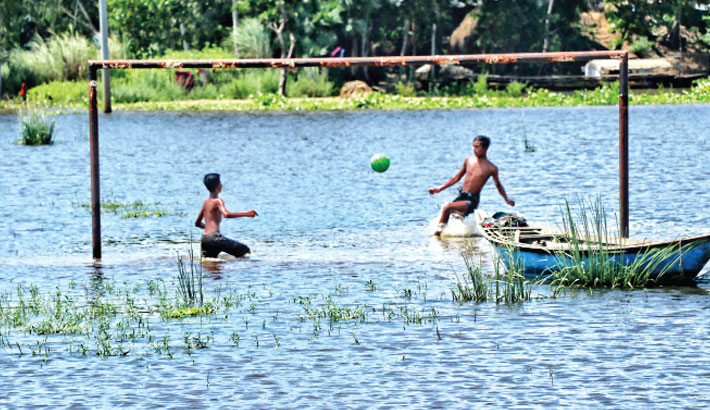 Two boys are having fun playing with a football in knee-deep water at a playground of a school in Kundail area under Tarash upazila of Sirajganj district on Saturday.   – PBA Photo