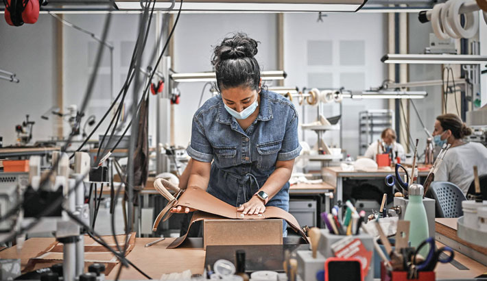 A woman works on a hand bag part at the new leather goods workshop of French high fashion luxury goods manufacturer Hermes, in Saint-Vincent-de-Paul, on Thursday, near Bordeaux, southwestern France, on the eve of its inauguration day.