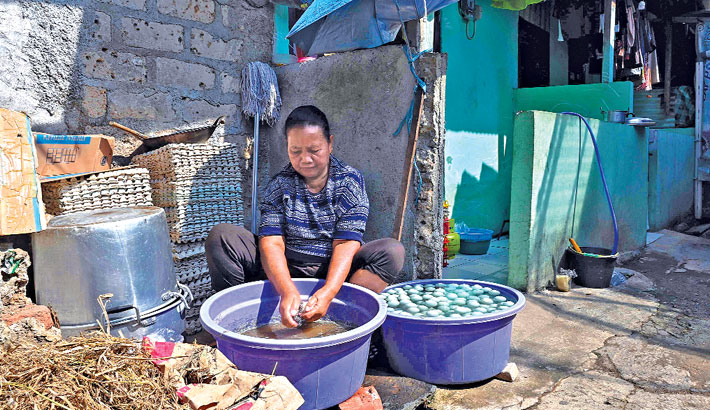 A woman cleans salted eggs to be sold in Jakarta on Monday.