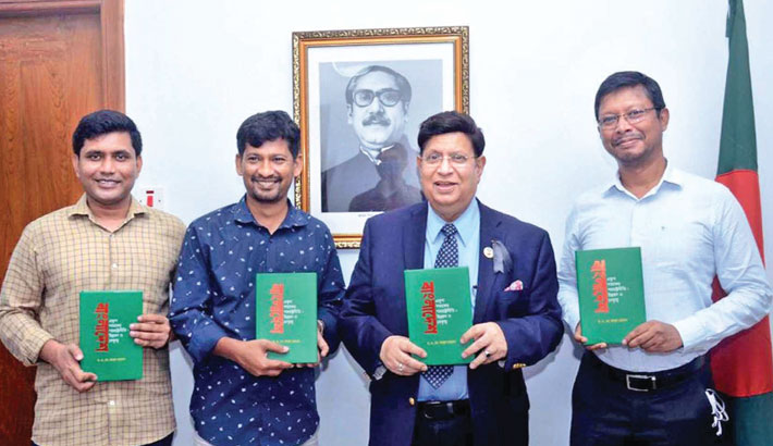 """Foreign Minister Dr AK Abdul Momen along with others holds copies of a book titled """"Bangladesh -- Ekush Shotoker Pororastro Niti: Unnoyon O Netritto"""" (Bangladesh -- Foreign Policy of the Twenty-first Century: Development and Leadership) by the minister at the book unveiling ceremony in the city on Monday."""