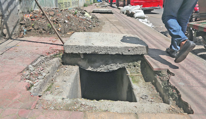 A manhole on a footpath in the capital's Motijheel area is lying in this condition as its lid has been removed, posing risk of accident. The photo was taken on Wednesday.     – Reaz Ahmed Sumon