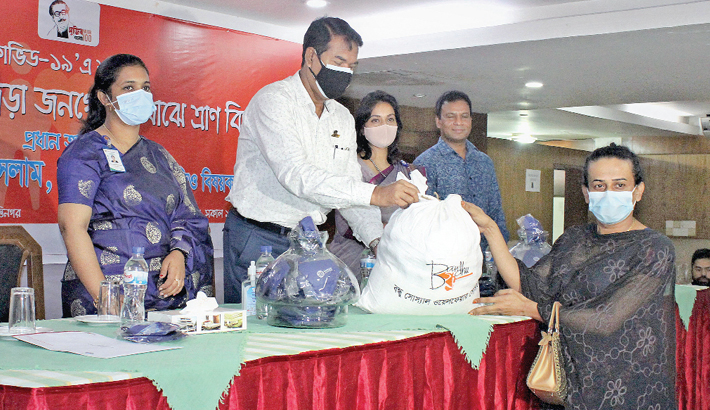 Director General of NGO Bureau KM Tariqul Islam (Additional Secretary) along with others hands over relief items to transgender people, who were affected by the Covid-19 pandemic, at a programme organised by Bandhu Social Welfare Society (Bandhu) in the city on Thursday.