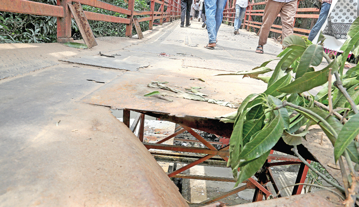 The footbridge connecting Kamalapur Railway Station with Mugda in the capital has turned into a death trap for pedestrians as a portion of the bridge has remained damaged for long. The photo was taken on Thursday.   -  Reaz Ahmed Sumon
