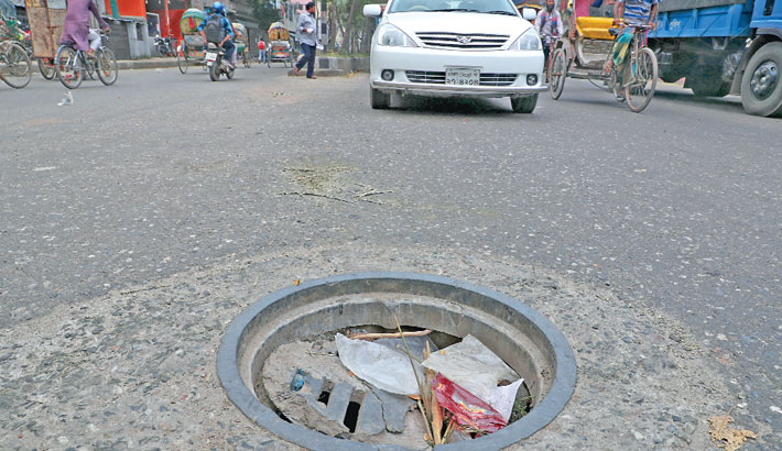 A manhole lies damaged for long on a busy road in the capital's Kamalapur area, posing risks of accident. The photo was taken on Tuesday. — sun photo