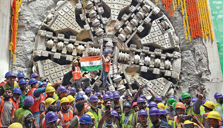 Construction workers celebrate after the Tunnel Boring Machine (TBM) 'Urja' emerged at the upcoming Shivaji Nagar underground metro  station after drilling a distance of 855 metres for over a year, in Bangalore on Wednesday.