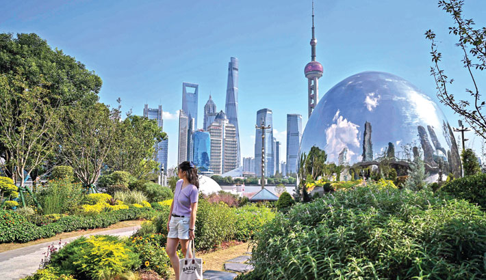 A woman poses for a picture for her family in a park as the Lujiazui financial district (back) is seen in Shanghai on Wednesday.
