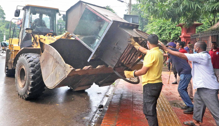 A DSCC bulldozer pulls a makeshift stall from a footpath during an eviction drive in front of Curzon Hall on Dhaka University campus on Wednesday. —SUN photo