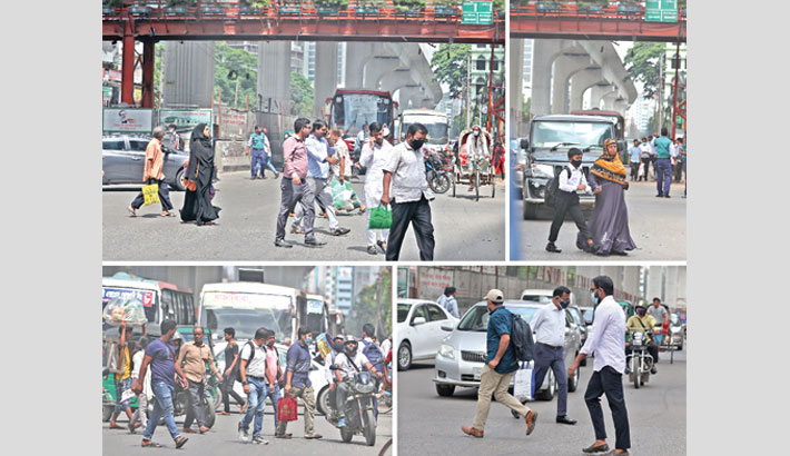 Pedestrians risk their lives to cross a busy road in the capital's Bangla Motor area instead of using a nearby footbridge on Wednesday. Reaz Ahmed Sumon