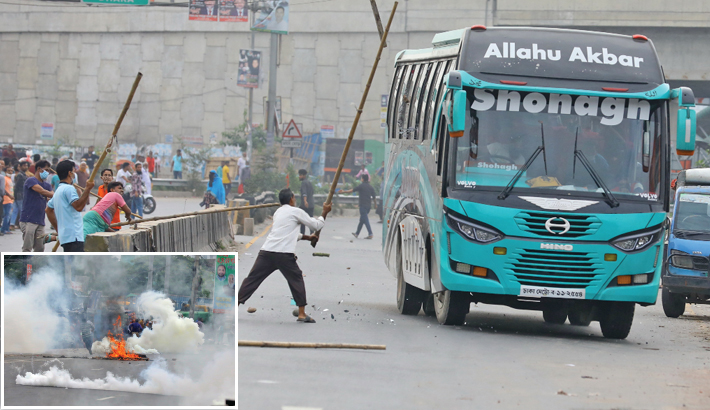 Agitated apparel workers vandalise a bus and block Dhaka-Sylhet highway by setting fire to tyres during a demonstration at Kanchpur in Narayanganj on Thursday, demanding payment of their due wages. —SUN photo