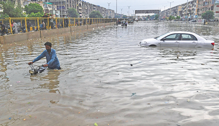 A man pushes his motorbike through a flooded street after a heavy rainfall in Karachi on Thursday.   — AFP PHOTO