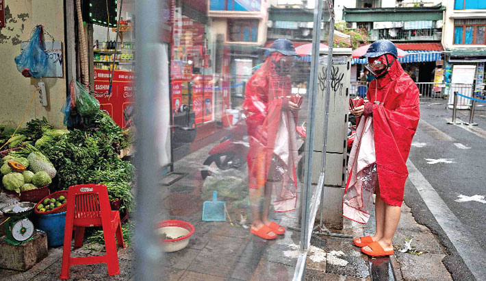 A woman shops from behind plastic sheets set up to minimise close contact at a wet market in the old quarters of Hanoi on Friday, following the easing of coronavirus restrictions after two months. — AFP Photo