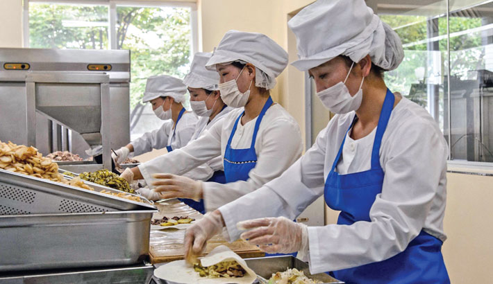 Employees produce wheat cakes stuffed with meat at the Kumsong Foodstuff Factory in Pyongyang on Saturday.