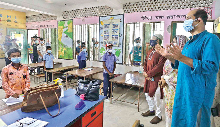 Dhaka North City Corporation Mayor Atiqul Islam speaks to students about hygiene at Malibagh Chowdhury Para Government Primary School in the capital on Saturday during his visit to Malibagh area to inspect the pesticide spraying activities to  contain Aedes mosquito. —SUN PHOTO