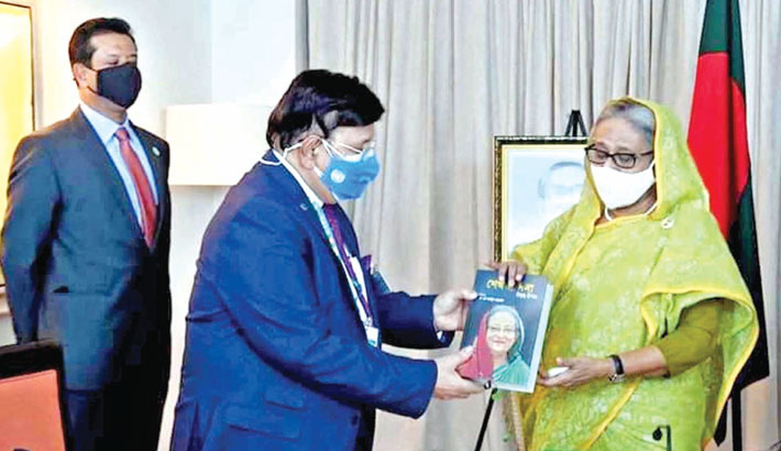Momen hands over his new book to PM
