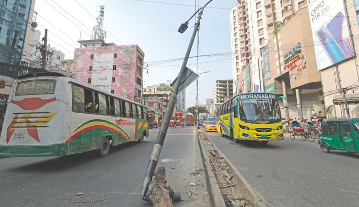 A street lamp post, which was damaged after being by a vehicle, is dangerously standing on the thoroughfare at Shahjadpur in the capital, posing risk of accident. The photo was taken on Sunday. – Kamrul Islam Ratan