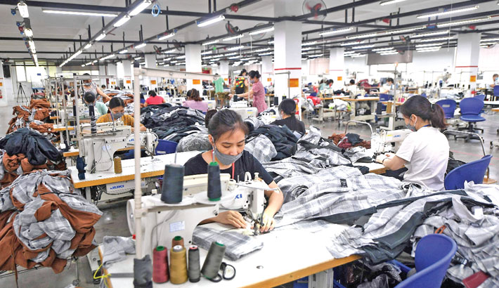 This photograph taken recently shows workers wearing face masks while working at the Maxport factory, which makes activewear for various textile clothing brands, in Hanoi.