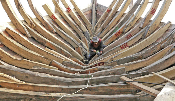 A worker builds a wooden fishing boat at a yard in Lhokseumawe, Aceh on Tuesday.