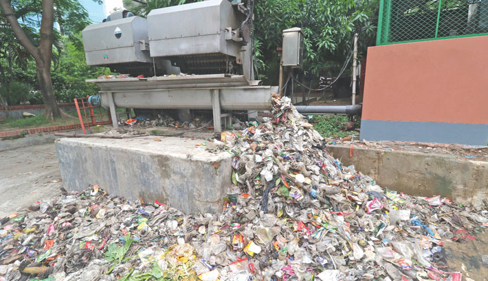 A machine at Hatirjheel sluice gate in the capital separates a huge amount of polythene and plastic materials from water everyday. A section of city people dump such waste materials into drains and the machine catches it. The photo was taken on Tuesday.  — SUN PHOTO