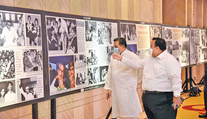 Finance Minister AHM Mustafa Kamal admires a photograph of Prime Minister Sheikh Hasina at an exhibition at a city hotel on Tuesday, marking the 75th birthday of the prime minister. Chowdhury Nafeez Sarafat, chairperson of the Board of Trustees of Canadian University of Bangladesh, was present on the occasion. —SUN photo
