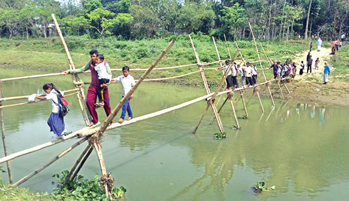 People, including school children, are crossing a bamboo bridge over the Sunai river Tilpara union under Beanibazar upazila of Sylhet. Around 40,000 people of the upazila use the 300 feet-long bridge, risking their lives. The photo was taken on Thursday. – Sun Photo