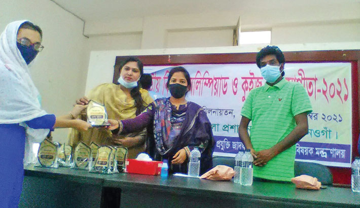 Badalgachi Upazila Nirbahi Officer Alpona Yeasmin hands over a crest to a winner of the 6th National Science Olympiad and Quiz Competition-2021 at a programme held in the upazila parishad auditorium on Thursday.  – Sun Photo