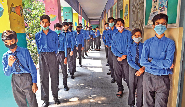Students stand in queues as they wait for their turn to receive a dose of Pfizer vaccine against the coronavirus at a school in Lahore on Friday, after the government began a drive to vaccinate children aged 12 and above. —AFP Photo
