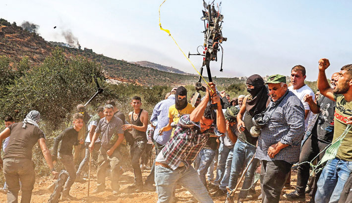 A Palestinian protester smashes an Israeli drone that reportedly fell because of a technical failure, during a demonstration against settlements in the West Bank village of Beita, on Friday. — AFP Photo
