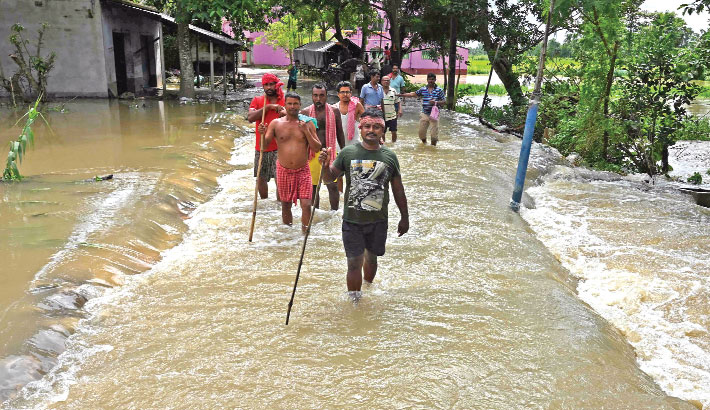 Flood affected villagers wade through a flooded area of Howrah district in India's West Bengal state on Saturday. — AFP PHOTO