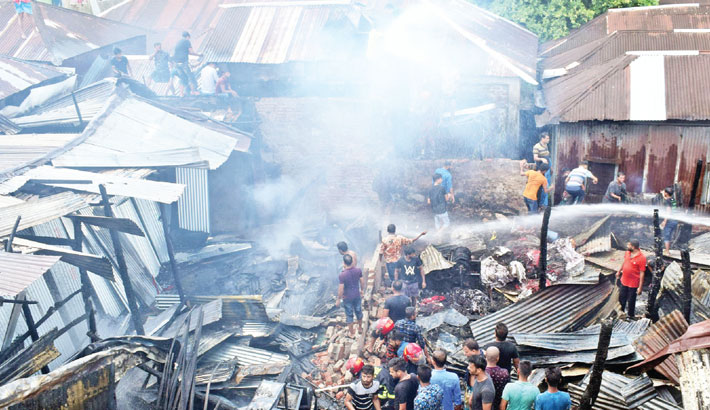 Firemen are trying to douse a fire that broke out at a market in Gaurnadi port of Barishal district on Saturday. Twelve shops were gutted by fire. – Star Mail Photo