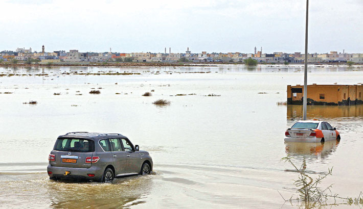 Vehicles make their way through a flooded street in the aftermath of tropical Cyclone Shaheen in Oman's northern town of al-Mussanah on Monday.  —AFP PHOTO