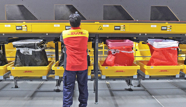 Employees works in a distribution centre at the new International logistics DHL Express air hub at the Roissy-Charles de Gaulle airport, outside Paris on Tuesday.