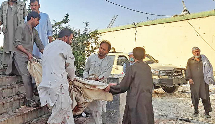 Afghan men carry the dead body of a victim to an ambulance after a bomb attack at a mosque in Kunduz on Friday. — AFP Photo