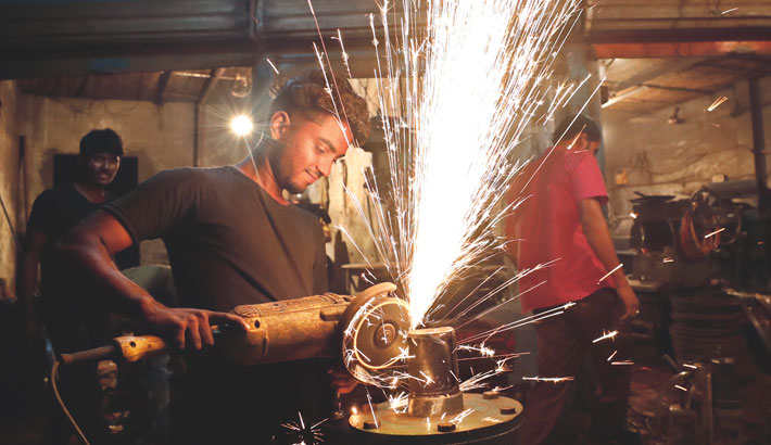 The scrape of a metal object with a machine at a workshop at Keraniganj on the outskirts of the capital has sent up a shower of sparks. This practice without any safety gear in place often causes damages to workers' eyes. The photo was taken on Saturday. – Kamrul Islam Ratan