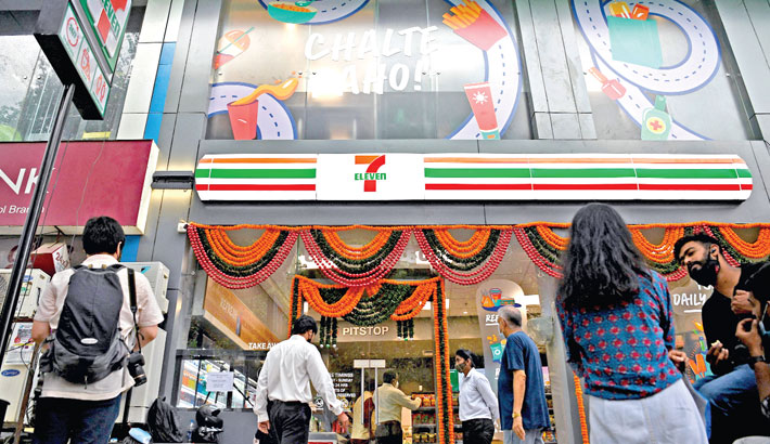 Customers enter inside the newly inaugurated India's first 7-Eleven convenience store in Mumbai on Saturday.