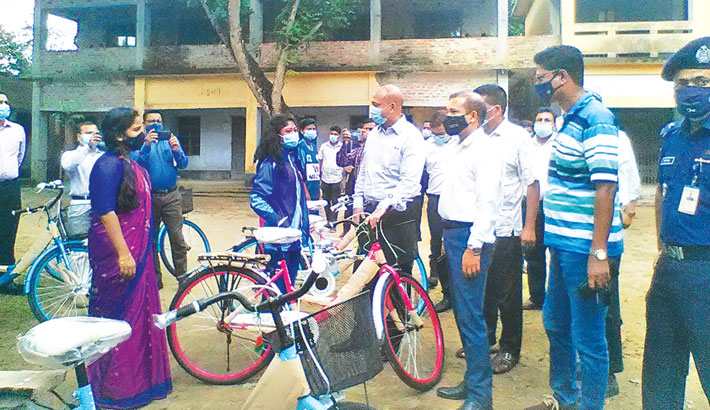 Rajshahi divisional commissioner Md Humayun Kabir distributes bicycles among 15 secondary level girl students of ethnic minority group in Badalgachhi Upazila of Naogaon district on Saturday. – Sun Photo