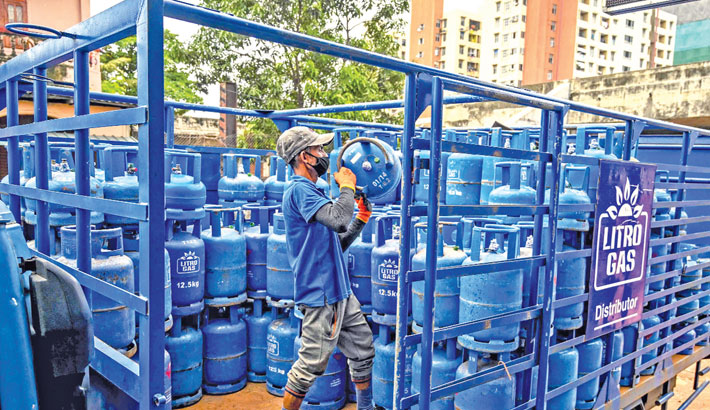 A worker loads a gas cylinder onto a truck at a gas outlet in Colombo on Monday.