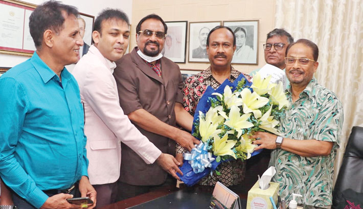 Jatiya Party Chairman GM Quader hands over a bouquet to newly-appointed secretary general of the party Mujibul Haque Chunnu at the party's Banani office on Tuesday. SUN PHOTO