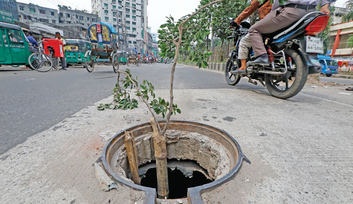 The lid of a manhole on the Inner Circular Road at Fakirerpool in the capital is missing only days after its installation. A branch of tree along with a bamboo pole has been placed to warn vehicles of impending danger. The photo was taken on Tuesday. – Kamrul Islam Ratan