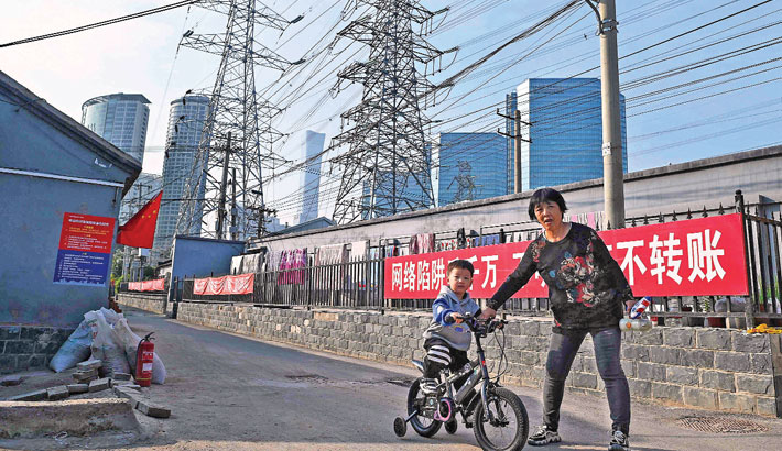 A woman guides a boy learning to cycle below power lines in Beijing on Wednesday.