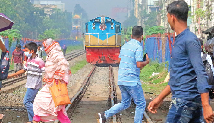 Crossing railway tracks even when a train is approaching fast is a common sight at different level crossings in the capital. In the photo taken from Mohakhali level crossing on Wednesday, people are seen making a desperate dash to cross the rail tracks risking their lives. — MD NASIR UDDIN