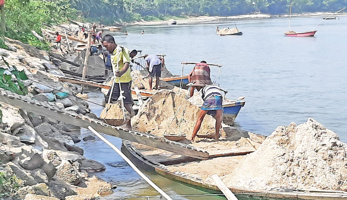 Labourers are unloading sands from boats on the bank of the Karatoya River in Panchagarh district. The photo was taken on Thursday. – Sun Photo