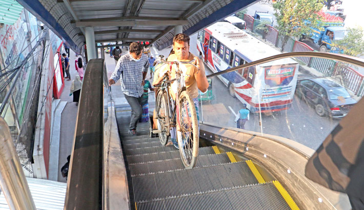 The escalator has been installed to help people, especially those with physical disorders, ascend the footbridge easily. However, a man is climbing up the escalator along with his bicycle, creating obstacles to other pedestrians. The photo was taken from Abrar Ahmed Chowdhury Memorial Footbridge at Pragati Sarani in the capital on Thursday.—Md Nasir Uddin