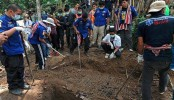Malaysia arrests 12 cops over link to migrants' mass graves